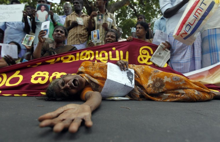 A Tamil woman cries as she holds up an image of her disappeared family member during the war against Liberation Tigers of Tamil Eelam (LTTE) at a protest in Jaffna on August 27, 2013. The demonstration was attended by 300 relatives of disappeared people and those who had lost lands was held outside the main library where U.N. Human Rights Commissioner Navi Pillay had a meeting. (Dinuka Liyanawatte/Reuters)