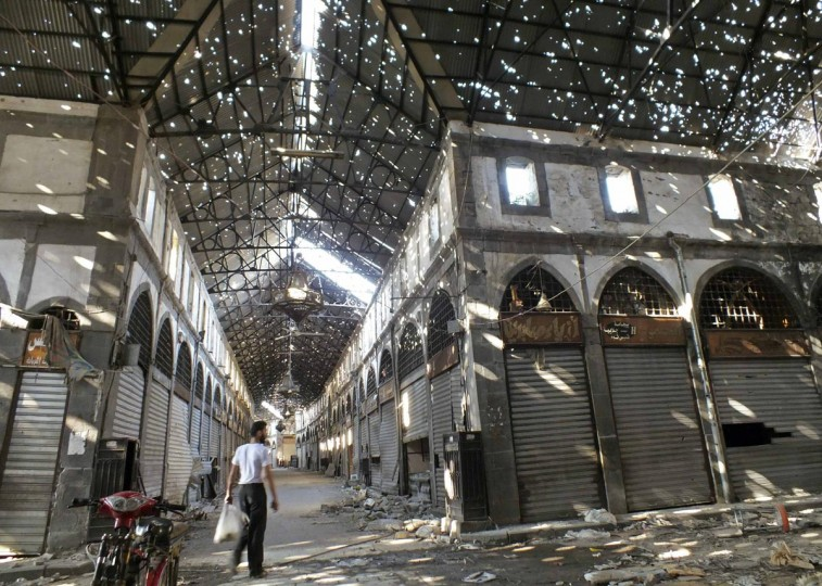A man walks inside the damaged historical old souk of Homs August 19, 2013. Picture taken August 19, 2013. (Yazan Homsy/Reuters)