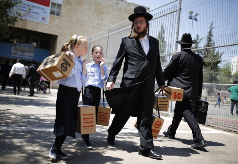 An ultra-Orthodox Jewish man walks out with his children after collecting gas mask kits at a distribution point in Jerusalem. Thousands of Israelis on Wednesday continued to queue up for gas masks or ordered them by phone, spurred on by fears that any Western military response to last week's alleged chemical weapons attack in Syria could ensnare their own country in war. Israel also deploying all of its missile defenses as a precaution against possible Syrian retaliatory attacks should Western powers carry out threatened strikes on Syria, Israeli Army Radio said on Wednesday. (Amir Cohen/Reuters)