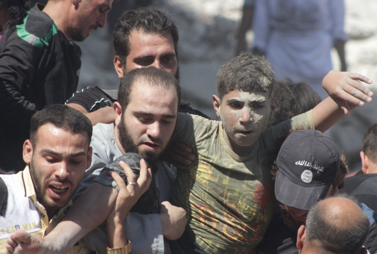 Men help a wounded boy rescued from under rubble after what activists said was shelling by forces loyal to Syria's President Bashar al-Assad in Aleppo's Bustan al-Qasr district, August 16, 2013. (Saad Abobrahim/Reuters)