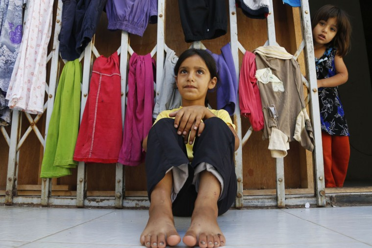 A Syrian refugee girl sits in front of hanging clothes as another girl looks on at a four-story mall housing refugees them in Deddeh village, northern Lebanon. Atop a mountain lined with olive and cypress trees overlooking Tripoli, Lebanon's second largest city, a disused shopping center houses nearly 1,000 Syrian refugees who have fled the civil war in recent months. The unending flow of refugees into Lebanon since the conflict began in March 2011 has led to the emergence of more than 1,400 informal settlements like this one across Lebanon. (Mohamed Azakir/Reuters)