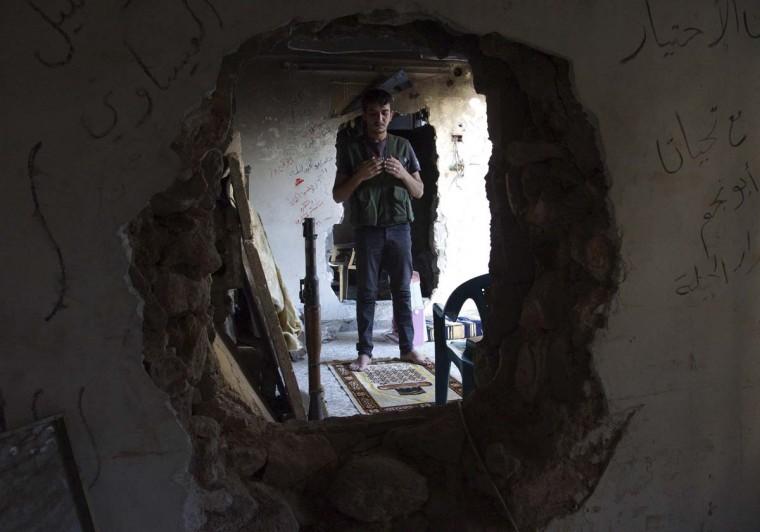 A Free Syrian Army fighter prays inside a room in Deir al-Zor. (Khalil Ashawi / Reuters)