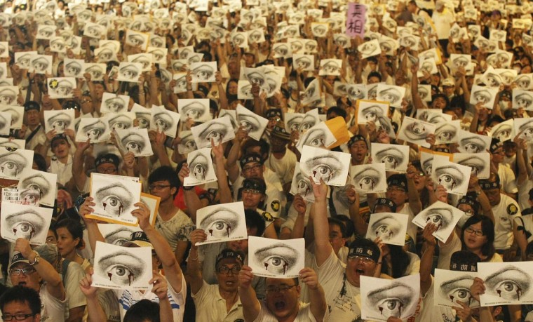 People, holding placards of a bleeding eye, take part in a demonstration in front of the Presidential Office in Taipei August 3, 2013. Hundreds of thousands of demonstrators gathered on Saturday to mourn for soldier Hung Chung-chiu, who died of severe heatstroke after being ordered to do strenuous exercises in a barracks on July 4, according to event organizers. (Steven Chen/Reuters)