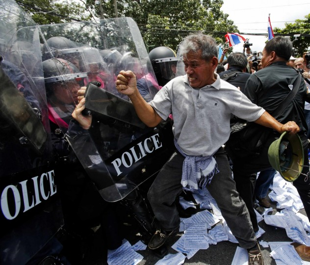 An anti-government protester clashes with riot police officers outside the parliament in Bangkok. Thailand's parliament was due to debate a political amnesty bill on Wednesday as anti-government protesters marched to try to get it scrapped, saying it could let ex-premier Thaksin Shinawatra return from exile without having to serve a jail sentence. (Athit Perawongmetha/Reuters)