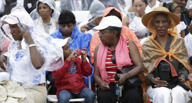 """Fredette West (2nd R) and her granddaughter Campbell West (2nd L), 6, take photographs during the 50th anniversary of the """"March on Washington"""" at the Lincoln Memorial in Washington August 28, 2013. Words from the first black U.S. president and bell ringing around the world on Wednesday will mark 50 years to the minute that civil rights leader Martin Luther King ended his landmark """"I have a dream"""" speech. (Gary Cameron/Reuters)"""
