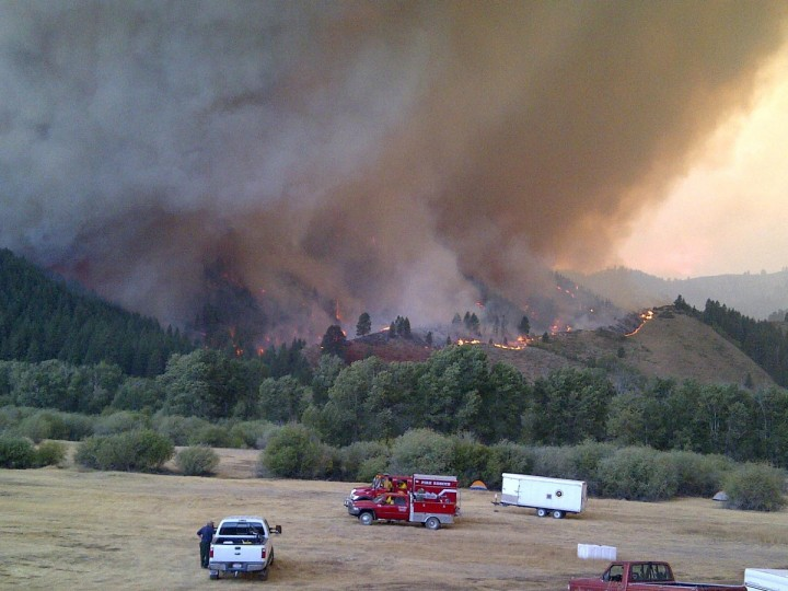 Smoke rises from the hills as the Elk Complex fire threatens an incident command post near Pine, Idaho in this August 12, 2013 handout photo provided by USFS. The fire has burned 90249 acres since being ignited by lightning strikes on August 8. Picture taken August 12, 2013. (USFS via Reuters)