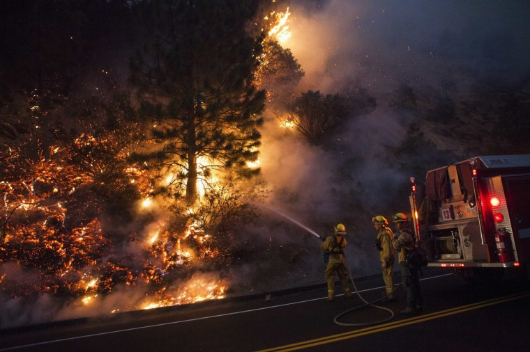 Firefighters work to prevent the Rim Fire from jumping Highway 120 near Buck Meadows, California, August 24, 2013. A fast-moving wildfire on the edge of Yosemite National Park has forced the closure of two more areas of the park, but an official said on Saturday he was cautiously optimistic that firefighters could halt the advance of flames. The fire, which had grown to just over 125,000 acres (50,585 hectares) as of early Saturday, remained largely unchecked with extreme terrain hampering efforts at containment, which stood at 5 percent. (Max Whittaker/Reuters)