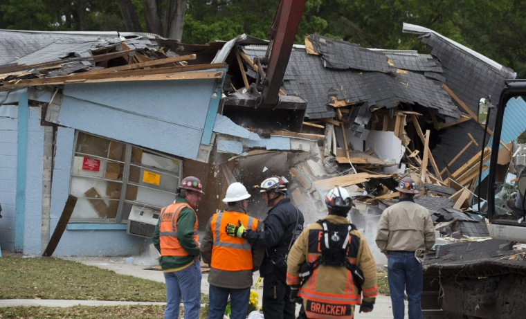 Demolition crews and Hillsborough County Fire Department watch as the house, where Jeffrey Bush was swallowed by a sinkhole, is demolished in Seffner, Florida March 3, 2013. Florida rescue workers ended their efforts on Saturday to recover the body of Jeffrey Bush, who disappeared into the sinkhole that swallowed his bedroom while he slept and demolished the suburban Tampa home due to its dangerous conditions, a rescue spokeswoman said. (Scott Audette/Reuters photo)