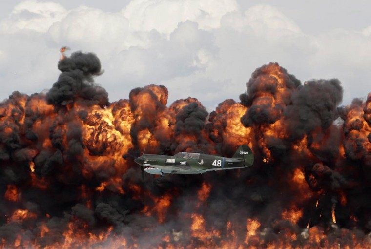 A World War II American plane flies in front of a wall of fire as it takes part in a re-enactment of the attack on Pearl Harbor during an afternoon air show at the EAA AirVenture at Wittman Regional Airport in Oshkosh, Wisconsin August 3, 2013. (Darren Hauck/Reuters)