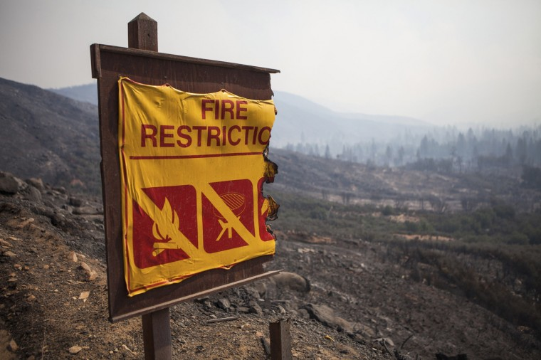 A fire restriction sign is partially burnt by the Rim Fire near Buck Meadows, California, August 22, 2013. The fire has burnt 53,866 acres northwest of Yosemite National Park. (Max Whittaker/Reuters)