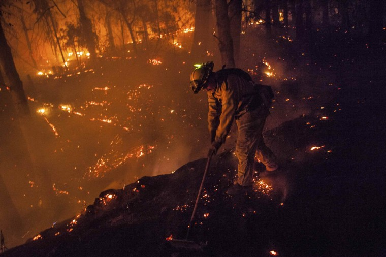 Firefighter Dave Beck rakes embers away from a road on the rim fire near Buck Meadows, California, August 22, 2013. (Max Whittaker/Reuters)
