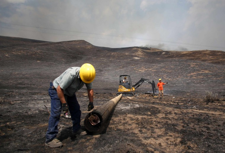 Idaho Power workers replace burned power poles at the Beaver Creek wildfire outside Hailey, Idaho August 17, 2013. A wildfire raging across the central mountains of Idaho forced the evacuation of 200 homes in the tourist town of Hailey on Saturday as fire-fighters lost ground against a blaze threatening the nearby international ski destination of Sun Valley. (Jim Urquhart/Reuters)