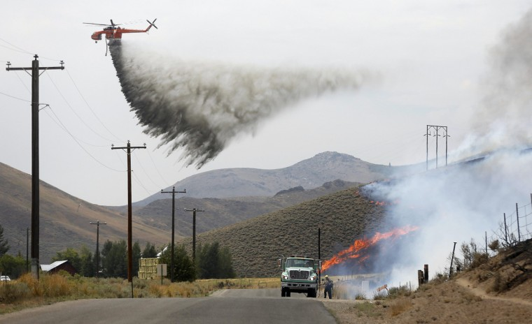 A tanker helicopter drops water as a firefighter works to douse a hot spot at the Beaver Creek wildfire outside Hailey, Idaho August 17, 2013. A wildfire raging across the central mountains of Idaho forced the evacuation of 200 homes in the tourist town of Hailey on Saturday as fire-fighters lost ground against a blaze threatening the nearby international ski destination of Sun Valley. (Jim Urquhart/Reuters)