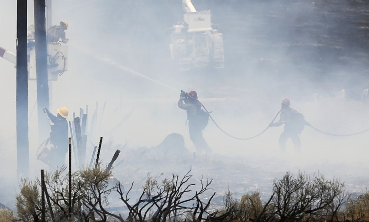 Idaho Power workers repair burned power lines as a fire crew works to douse a hot spot at the Beaver Creek wildfire outside Hailey, Idaho August 17, 2013. A wildfire raging across the central mountains of Idaho forced the evacuation of 200 homes in the tourist town of Hailey on Saturday as fire-fighters lost ground against a blaze threatening the nearby international ski destination of Sun Valley. (Jim Urquhart/Reuters)