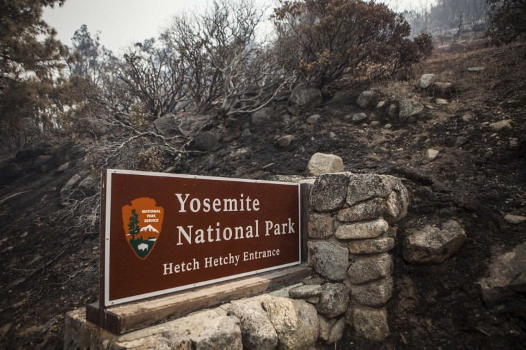 A sign on the edge of Yosemite National Park, California, is surrounded by a burn from the Rim Fire, August 23, 2013. The 105,000-acre Rim Fire, named for a Stanislaus National Forest lookout point called Rim of the World, has destroyed four homes and 12 outbuildings since it broke out on Saturday. It had blackened 11,000 acres at the northeastern edge of Yosemite as of Friday, park spokeswoman Kari Cobb said. (Max Whittaker/Reuters)