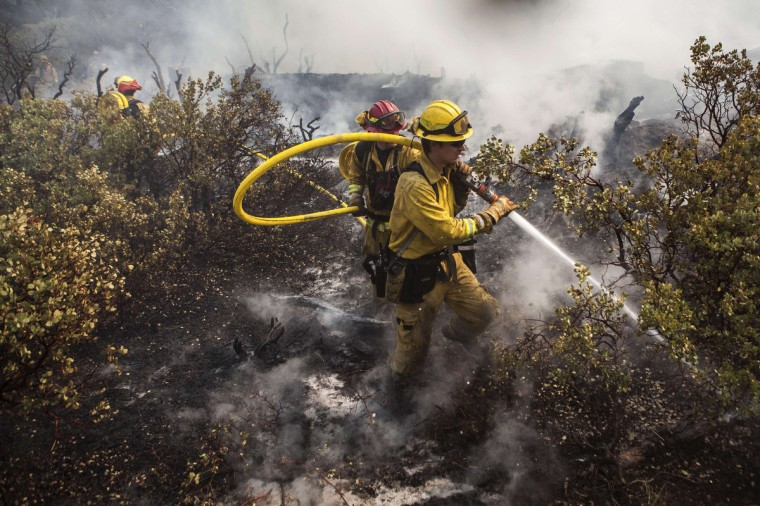 A firefighting crew puts out a spot fire that jumped a fire line in Yosemite National Park, California, August 23, 2013. The 105,000-acre Rim Fire, named for a Stanislaus National Forest lookout point called Rim of the World, has destroyed four homes and 12 outbuildings since it broke out on Saturday. It had blackened 11,000 acres at the northeastern edge of Yosemite as of Friday, park spokeswoman Kari Cobb said. (Max Whittaker/Reuters)