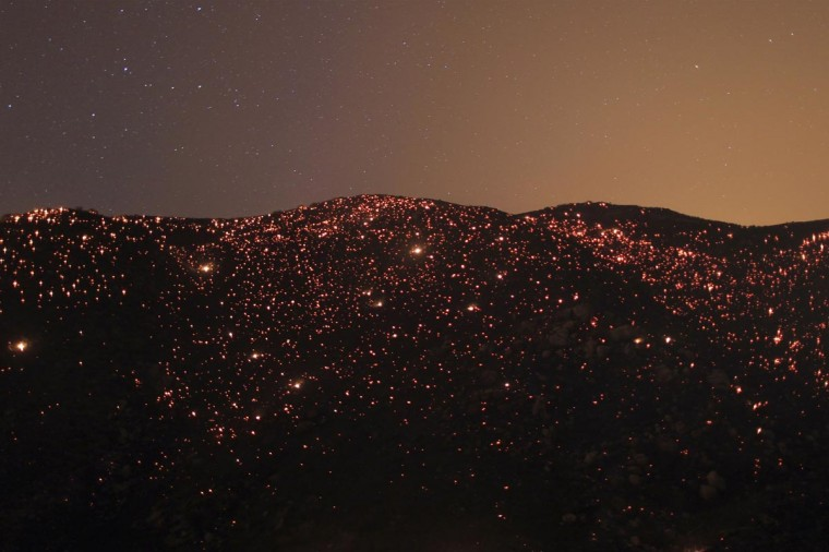 A smoldering mountainside is seen under the stars at the Silver Fire near Banning, California August 7, 2013. The fire broke out shortly after 2 p.m. near a back-country road south of Banning, about 90 miles outside Los Angeles in Riverside County, and within hours had blackened more than 5,000 acres, California Department of Forestry and Fire Protection spokesman Daniel Berlandt said. (David McNew/Reuters)