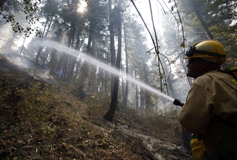 Firefighter Henry Munoz sprays down a hotspot at the Elk Complex wildfire outside Boise, Idaho. Together with the Elk, Pony, Beaver Creek and McCan wildfires over 300,000 acres have burned between Boise and Hailey, Idaho. (Jim Urquhart/Reuters)
