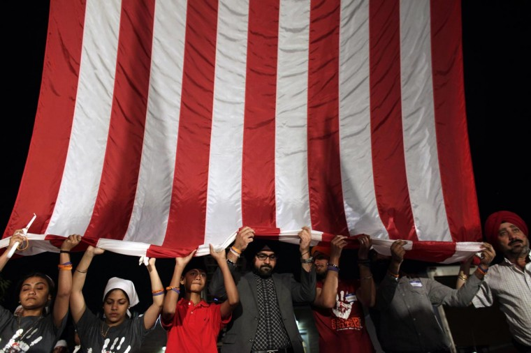 Family members of those killed hold a American flag as mourners attend a candlelight vigil on the one-year anniversary of a mass shooting at the Sikh Temple of Wisconsin, in Oak Creek, Wisconsin August 5, 2013. Gunman Wade Michael Page killed six members of the Sikh temple in 2012 before shooting himself dead. (Darren Hauck/Reuters)