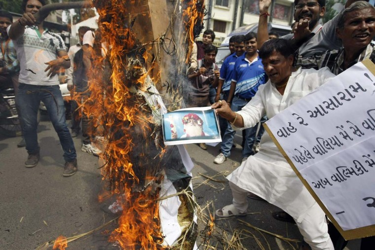 Protesters burn an effigy depicting spiritual leader Asaram Bapu during a protest in the western Indian city of Ahmedabad. According to local news reports, Asaram Bapu has been booked for sexual assault on a 16-year-old inmate at an ashram in Jodhpur run by Bapu's trust. Bapu's spokesman has denied the charges. (Amit Dave / Reuters)