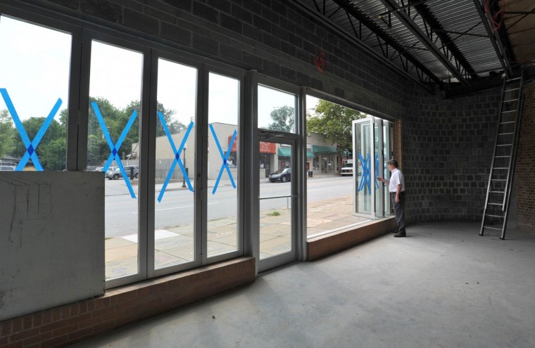 Buzz Cusack opens the folding windows which look out onto the sidewalk of York Road where additional seating will be added in the new wine bar addition to the Senator Theatre. (Amy Davis /Baltimore Sun)