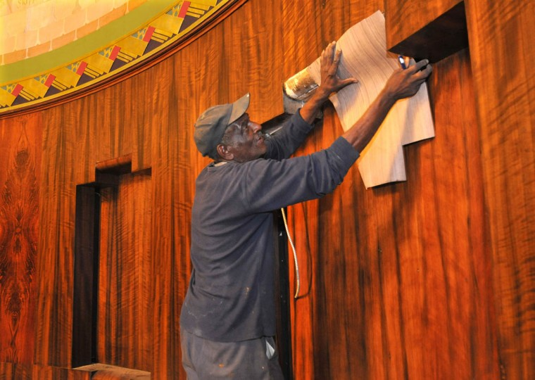 Craftsman Norman Wesson takes a measurement from the walnut veneer paneling that he restored in the lobby. (Amy Davis /Baltimore Sun)