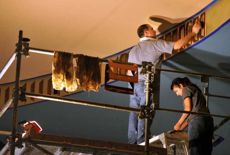 Tim Phebus and Elisha Rowe of Thomas Moore Studios use a stencil to paint trompe l'oeil chevrons on the ceiling return in the main auditorium. (Amy Davis /Baltimore Sun)