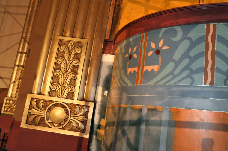 Artist Thea Osato repainted the stenciled designs on columns near the stage in the original auditorium. (Amy Davis /Baltimore Sun)