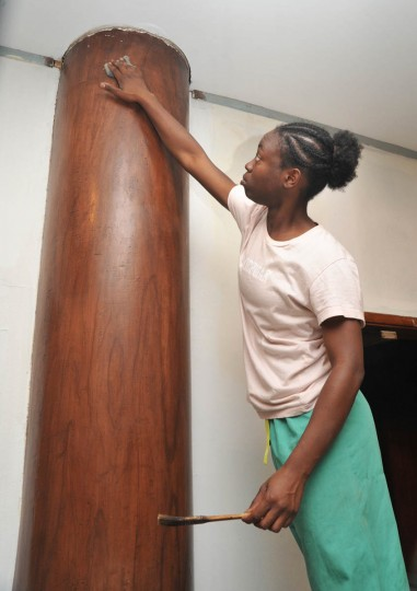 Jessica Turner rubs down a column in the inner lobby to add patina to the faux wood finish. She has been working under the tutelage of Norman Wesson. (Amy Davis /Baltimore Sun)