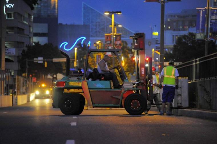 Workers install concrete barriers on Conway Street Tuesday, Aug. 6, 2013, for the upcoming Labor Day weekend Baltimore Grand Prix. (Karl Merton Ferron/Baltimore Sun)