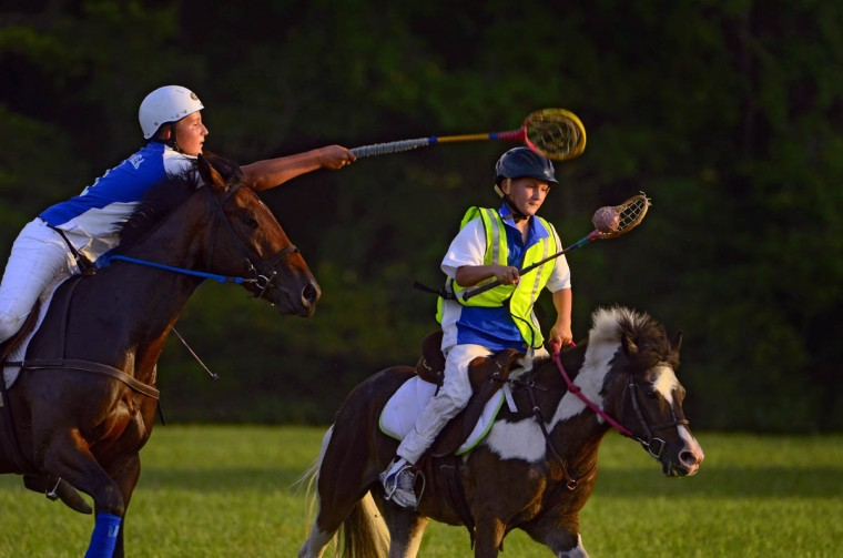 Tristan Cole, 10, riding Cherokee, turns to avoid the stick check of his brother Becher Cole, 13, riding Dan, during practice. (Karl Merton Ferron/Baltimore Sun)