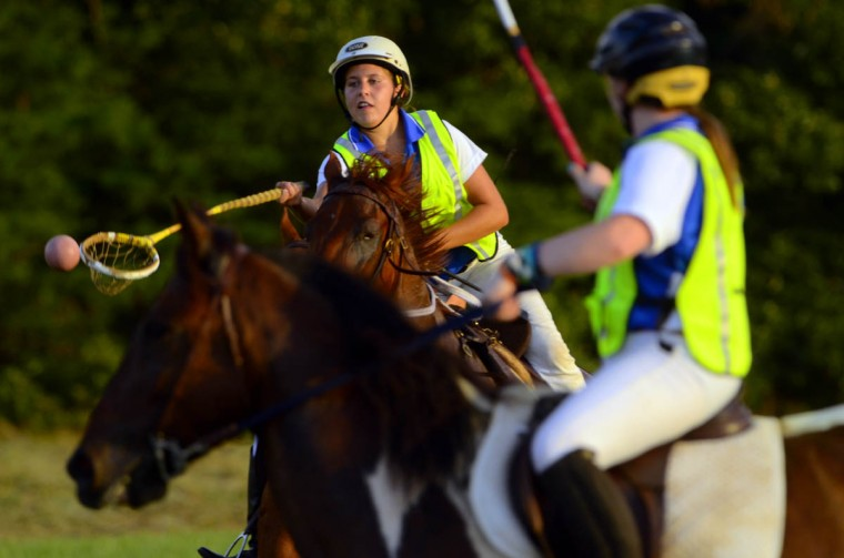 Megan Waggener, riding Domino, passes the ball to a teammate during practice at an open field in southern Maryland. (Karl Merton Ferron/Baltimore Sun)