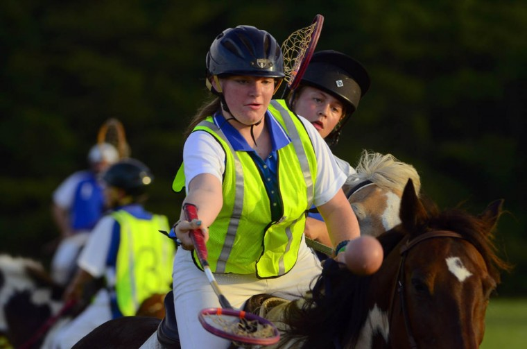 Sabrina Dobbins, 15, riding Oliver, shoots to score in front of Quinn Riddle, 14, riding Pony (background), during practice at an open field in southern Maryland. (Karl Merton Ferron/Baltimore Sun)