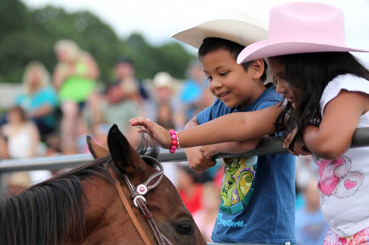 Zachary Purich, left, 6, of Laurel, and his friend Fatima Kahn, right, 7, of Pakistan, pet a horse before the start of the event. (Jen Rynda/BSMG)