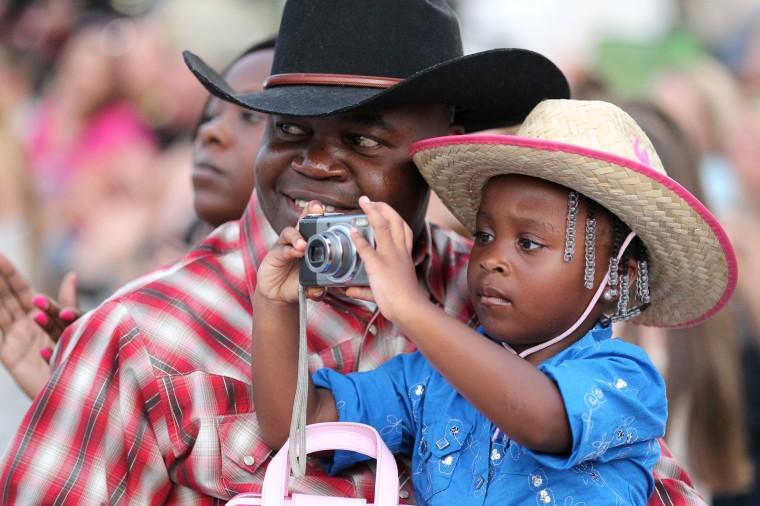 "West Friendship, MD 080513 Staff Photo by Jen Rynda David Akinabu, left, of Mount Washington, and his daughter, London, 4, watch as the ""Bull Blast! 2013"" starts at the Howard County Fair. (Jen Rynda/BSMG)"