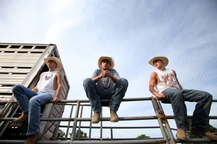 Dylan Hightman, left, Justin Reed, center, 17, and Justin Stonestreet, right, 17, all of Middletown sit near the bulls before the Bull Blast. (Jen Rynda/BSMG)