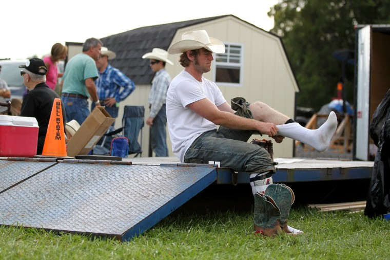 """Bull rider Andrew Griffith, of Boonsboro, puts his socks on before he competes in the """"Bull Blast! 2013"""" at the Howard County Fair in West Friendship, on Monday, August 5, 2013. (Jen Rynda/BSMG)"""