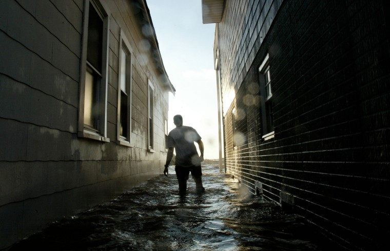 Jim Bradshaw walks in between his house and his neighbor's flooded by the Chesapeake Bay from the surge of Hurricane Isabel September 19, 2003 in North Beach, Maryland. Isabel gave the Maryland bay area the highest flooding in recent memory. (Mark Wilson/Getty Images)