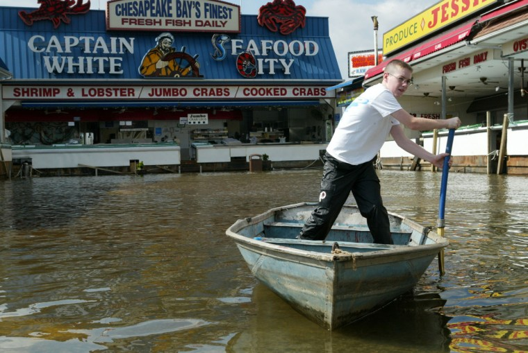Pete White uses his boat on the flooded waters at the water-front seafood market September 19, 2003 in Washington, DC. Clean up continues in the region after Hurricane Isabel left millions along the Atlantic coast without power and at least 15 people dead. (Alex Wong/Getty Images)