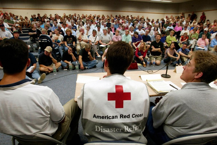 An unidentified Red Cross Information representative (C front) joins police, fireman, water and electrical representatives that brief over 500 Alexandria residents on restoring their services, at the Whitman Middle School 20 September 2003 in Alexandria, VA. The Alexandria area was the hardest hit by Hurricane Isabel in the Northern Virginia area leaving over one million people affected. (Stephen Jaffe/Getty Images)