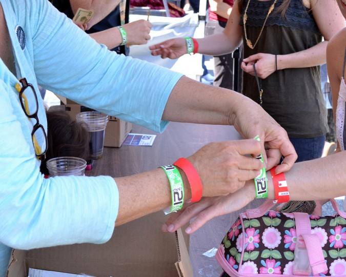 "An ID station worker secures an ""Over 21"" bracelet around the wrist of a festival goer April 27 at the inaugural Charm City Folk and Bluegrass Festival at Union Craft Brewing in Woodberry. (Steve Earley/Baltimore Sun)"
