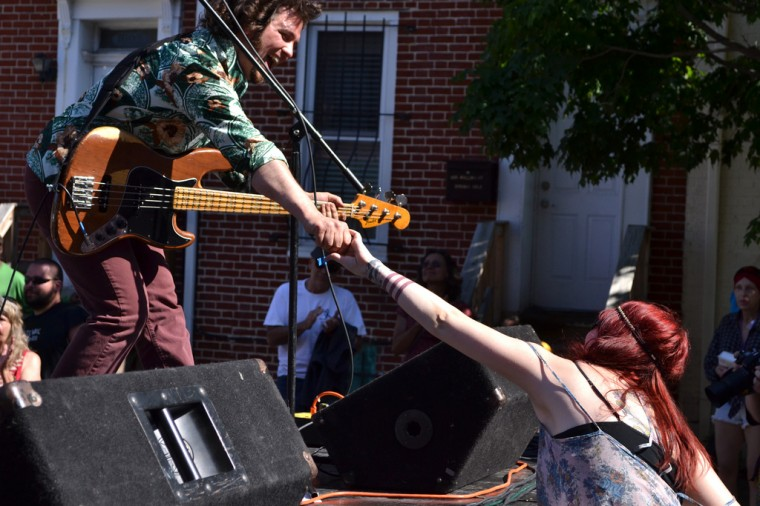 Sweet Leda bassist Jamie Horrigan greets a friend while performing on the RiseUp Stage at the SoWeBo Arts and Music Festival. (Steve Earley/Baltimore Sun)