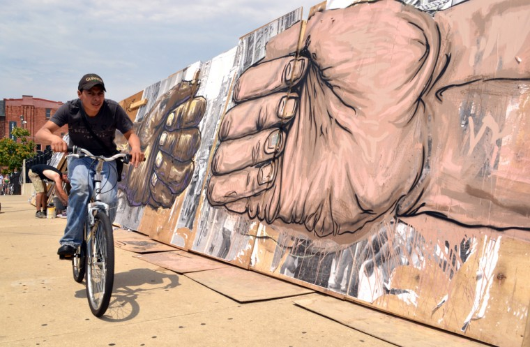 Many Artscape attendees who passed this mural by Stefan Ways on July 20 on the Charles Street bridge seemed moved by the artist's statement. (Steve Earley/Baltimore Sun)