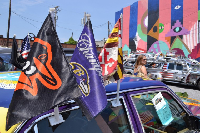 Flags on an Artscape art car represent Maryland and its two major pro sports teams. (Steve Earley/Baltimore Sun)