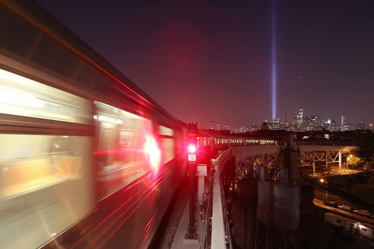 New York City's Tribute In Light shines in Manhattan (R) as a Brooklyn subway passes on the eve of the twelfth anniversary of the terrorist attacks at the World Trade Center on September 10, 2013 in New York City. (Mario Tama/Getty Images)