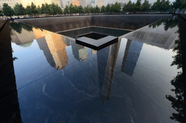 Building are reflected in one of the pools of the 9/11 Memorial during ceremonies for the twelfth anniversary of the terrorist attacks on lower Manhattan at the World Trade Center site on September 11, 2013 in New York City. The nation is commemorating the anniversary of the 2001 attacks which resulted in the deaths of nearly 3,000 people after two hijacked planes crashed into the World Trade Center, one into the Pentagon in Arlington, Virginia and one crash landed in Shanksville, Pennsylvania. Following the attacks in New York, the former location of the Twin Towers has been turned into the National September 11 Memorial & Museum. (Alejandra Villa/Getty Images)