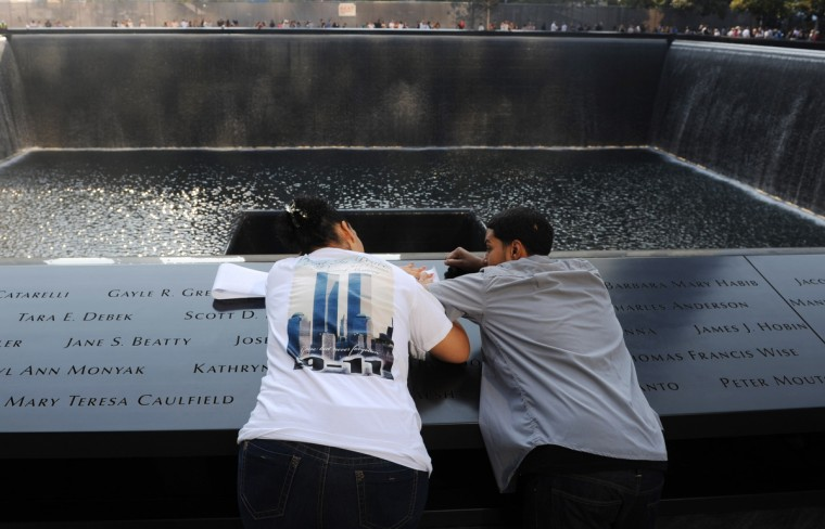 Shanhellen Jiminez (L) of Brooklyn, who lost her mother Elena Ledesma on 9/11, makes a rubbing of her mother's name at the 9/11 Memorial during ceremonies for the twelfth anniversary of the terrorist attacks on lower Manhattan at the World Trade Center site on September 11, 2013 in New York City. (David Handschuh/Getty Images)