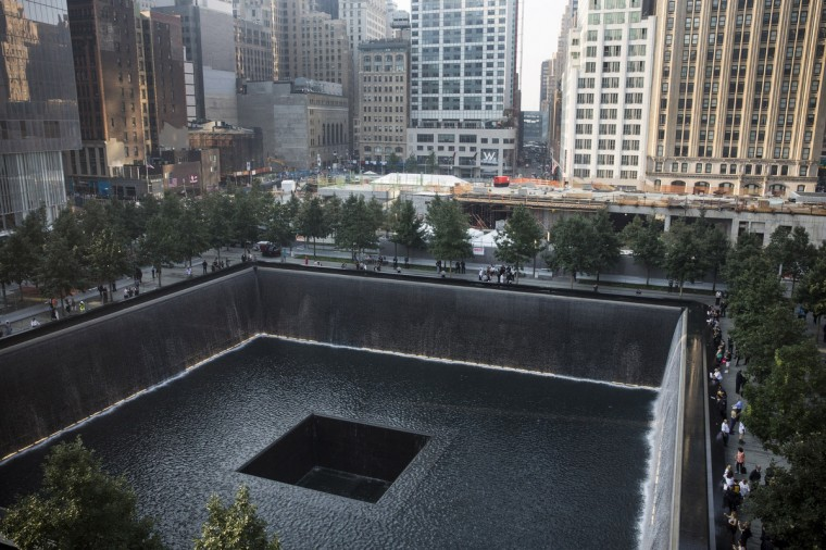 People gather around the South Tower pool during memorial ceremonies for the twelfth anniversary of the terrorist attacks on lower Manhattan at the World Trade Center site on September 11, 2013 in New York City. (Andrew Burton/Getty Images)