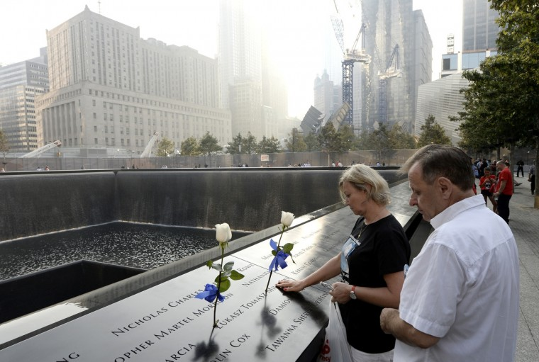 A couple pauses along the edge of the North Pool at the 9/11 Memorial during ceremonies for the twelfth anniversary of the terrorist attacks on lower Manhattan at the World Trade Center site on September 11, 2013 in New York City. (Justin Lane/Getty Images)