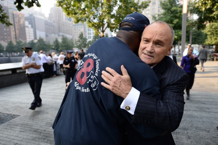 New York City Police Commissioner Ray Kelly (R) hugs a friend at the South Tower reflecting pool of the 9/11 Memorial during ceremonies for the twelfth anniversary of the terrorist attacks on lower Manhattan at the World Trade Center site on September 11, 2013 in New York City. (Stan Honda/Getty Images)